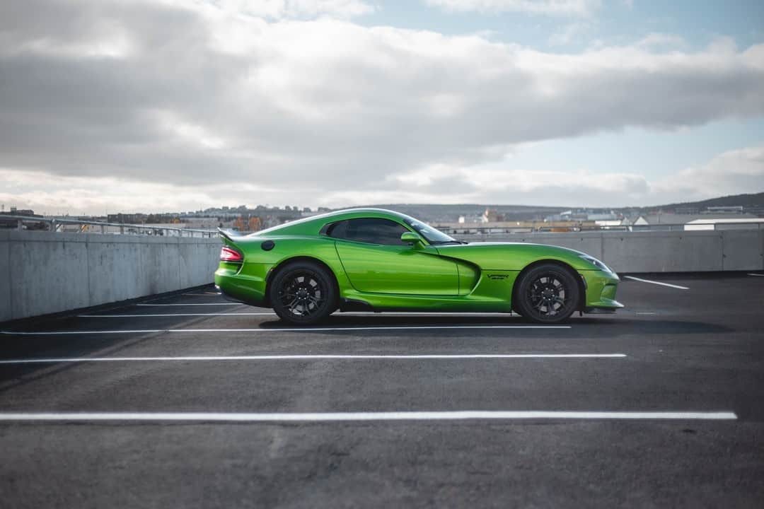A green car parked on the side of a road